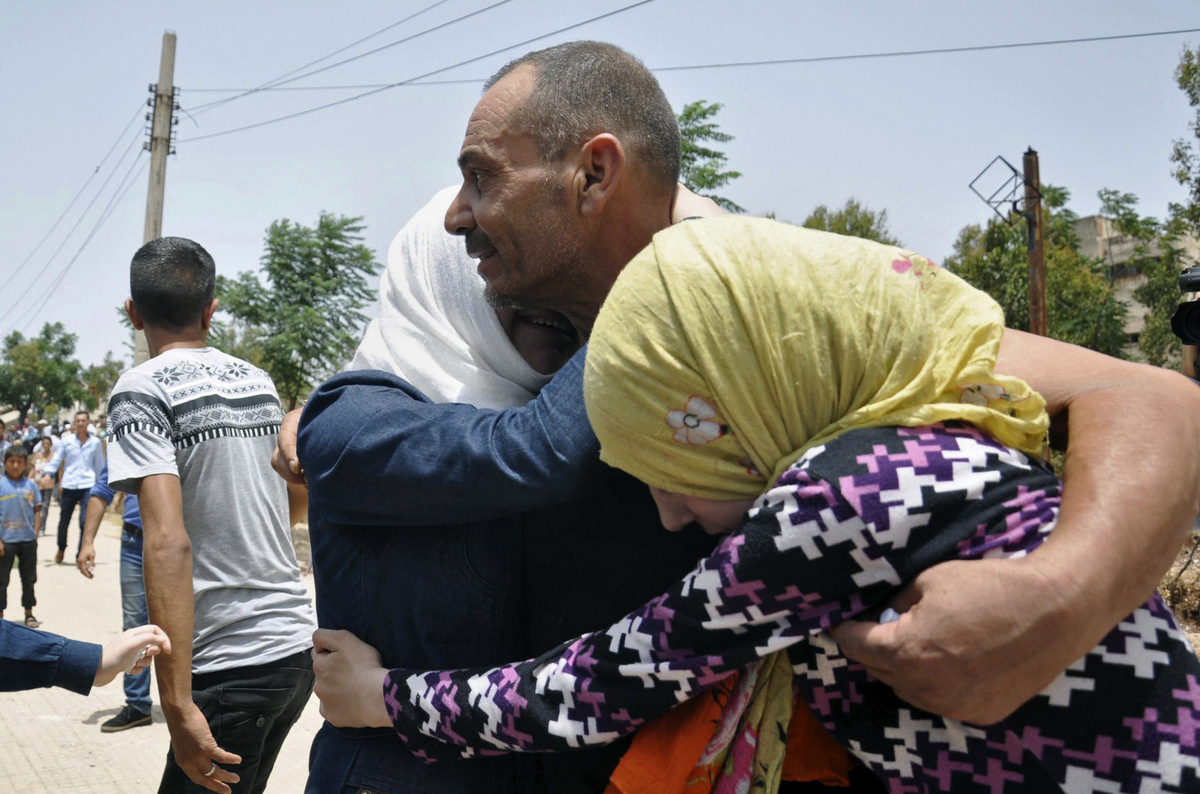 A Syrian family embracing after arriving from Jarablus, in Aleppo province, to their old neighborhood of al-Waer, in Homs, Syria, July. 11, 2017. (SANA via AP)