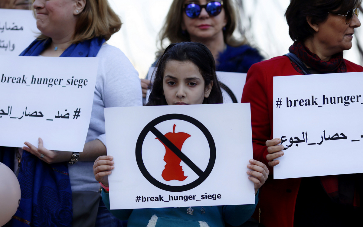Anti-Syrian government activists hold up placards during a protest in front of the European Union embassy in Beirut after harrowing pictures in the media of emaciated children were blamed on a siege of the town of Madaya by Syiran troops.(AP/Hassan Ammar)