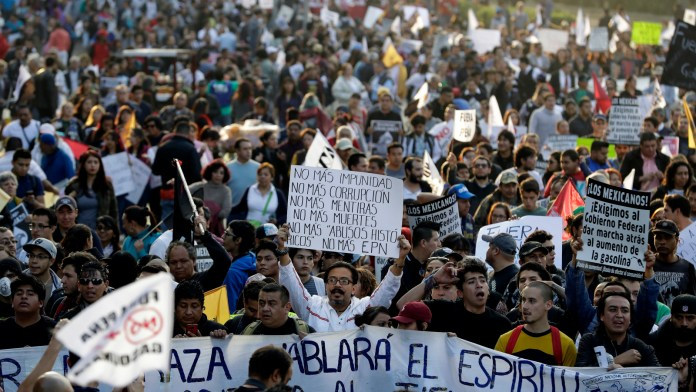 """A man carries a sign reading in Spanish """"No more impunity, no more corruption, no more lies, no more death, no more 'historic abuses,' no more EPN,"""" as thousands marched in anger against the government of Enrique Pena Nieto following a 20 percent rise in gas prices, in Mexico City, Jan. 9, 2017. (AP/Rebecca Blackwell)"""