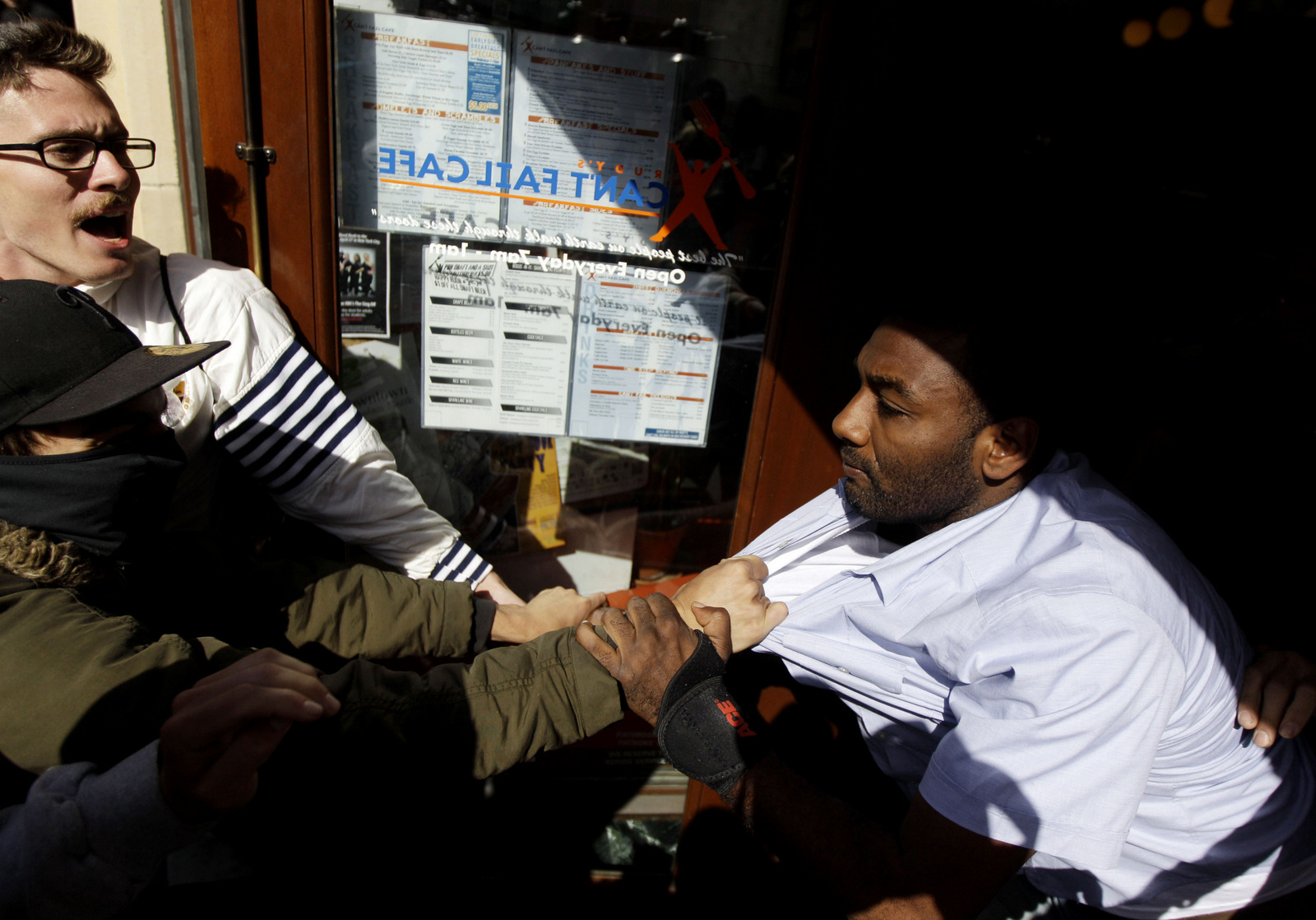 A storekeeper (right) clashes with Occupy Oakland protesters trying to shut down a coffee shop during May Day protests on, May 1, 2012 in Oakland, Calif. Marcio Jose Sanchez | AP