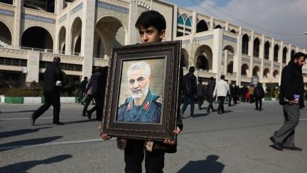"A boy carries a portrait of Gen. Qassem Soleimani in Tehran, Iran, Jan. 3, 2020. Iran has vowed ""harsh retaliation"" for the assassination of Soleimani. Vahid Salemi | AP"