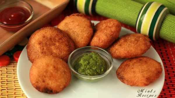 Suji ki kachori on a white plate with some green chutney oh the center of the plate putted on a mat with a dark greenish shade on the background | www.mintsrecipes.com |