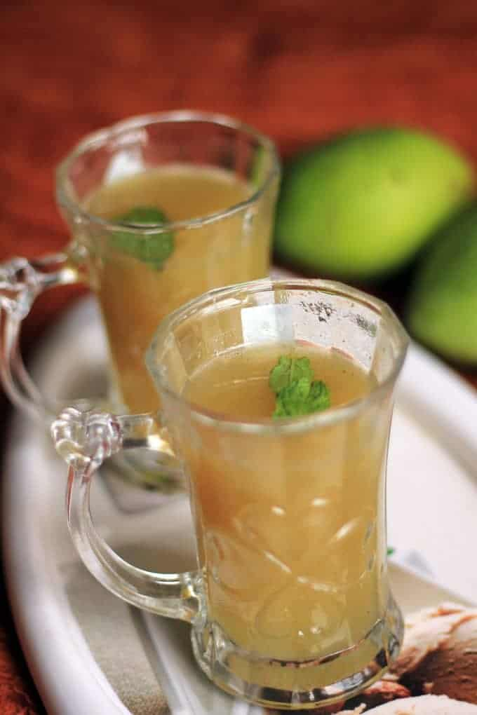 Aam Ka Panna on a transparent glass with some mints leaf keeped on a white tray with some raw mango on the background  
