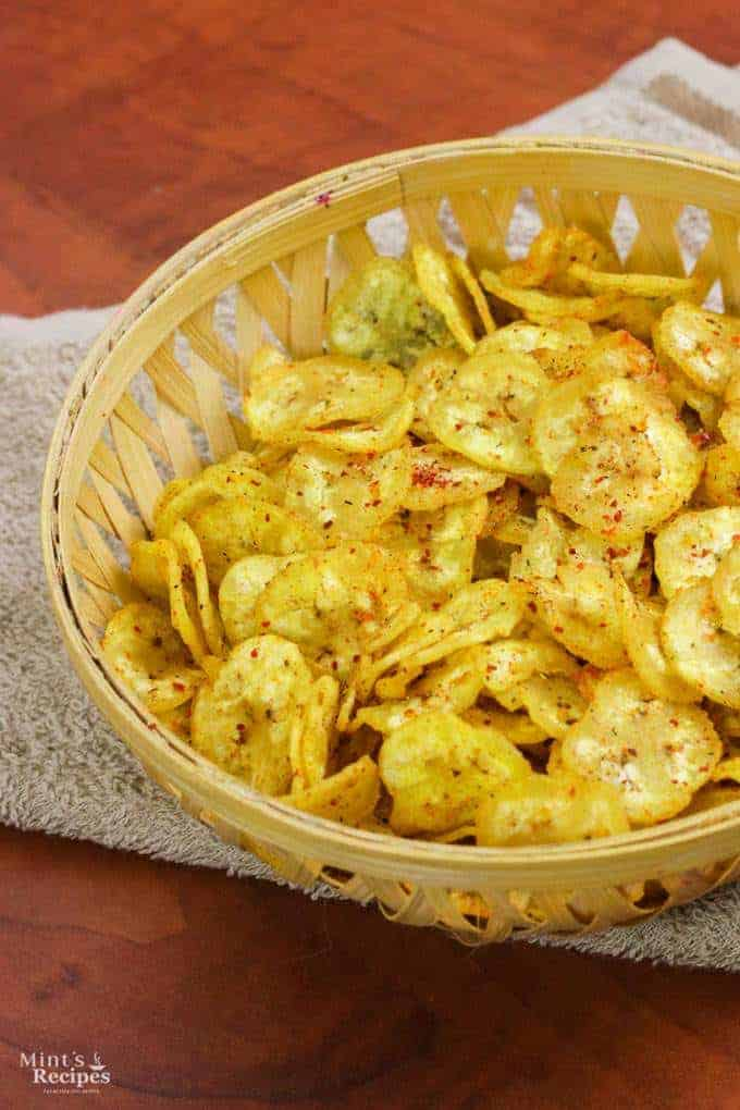 Banana Chips on a wooden basket full of banana chips kept on a handkerchief on wooden surface |