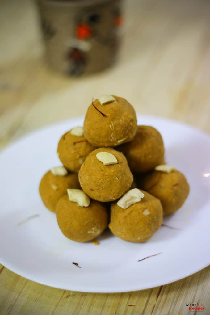 Besan Ke Laddu on a white plate with some cashew and saffron used to garish the laddu kept on a wooden surface