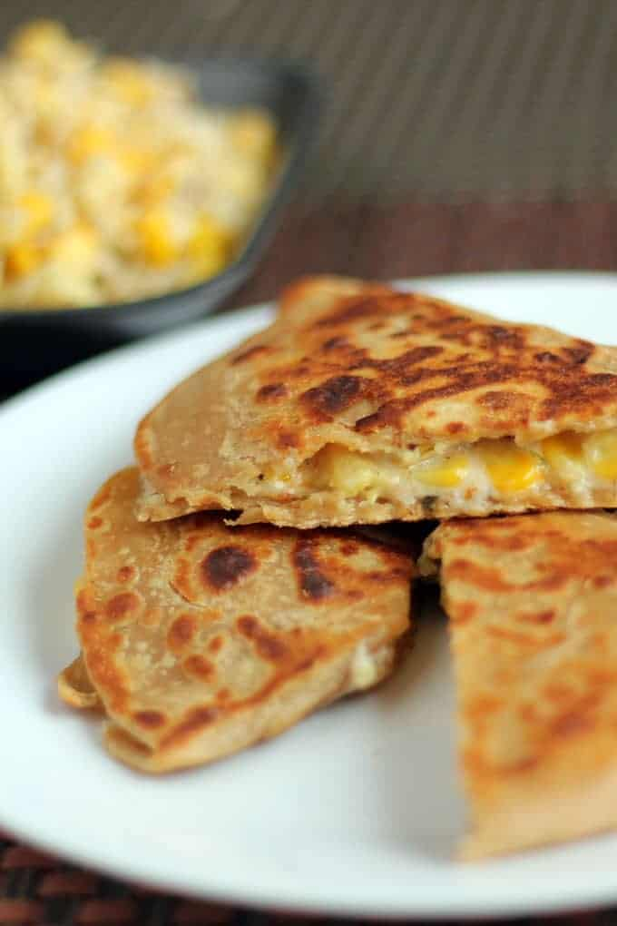 Cheese Corn Pizza Paratha on a white plate with dark background with some cheese corn mixture