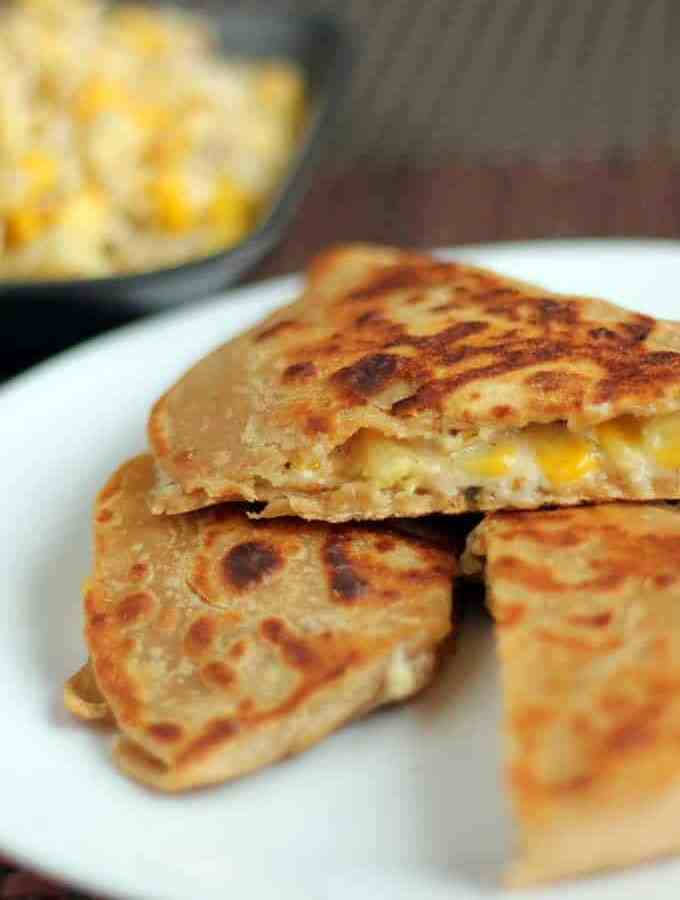 Cheese Corn Pizza Paratha on a white plate with dark background with some cheese corn mixture | www.mintsrecipes.com |