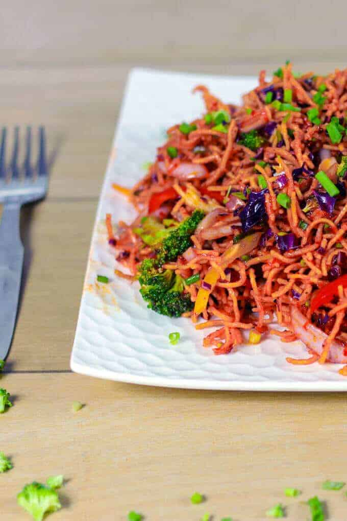 Chinese salad on a white plate garnishing with some spring onion and broccoli kept on wooden surface