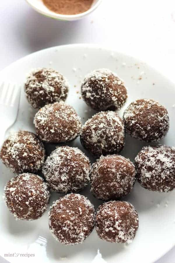Chocolate coconut balls on a white plate garnished with some dessicated coconut