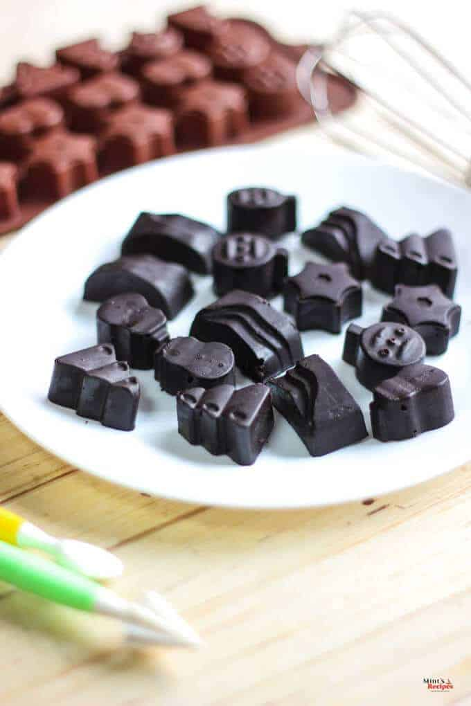 Chocolates on a white plate with a chocolate mould and wire whisker in the background