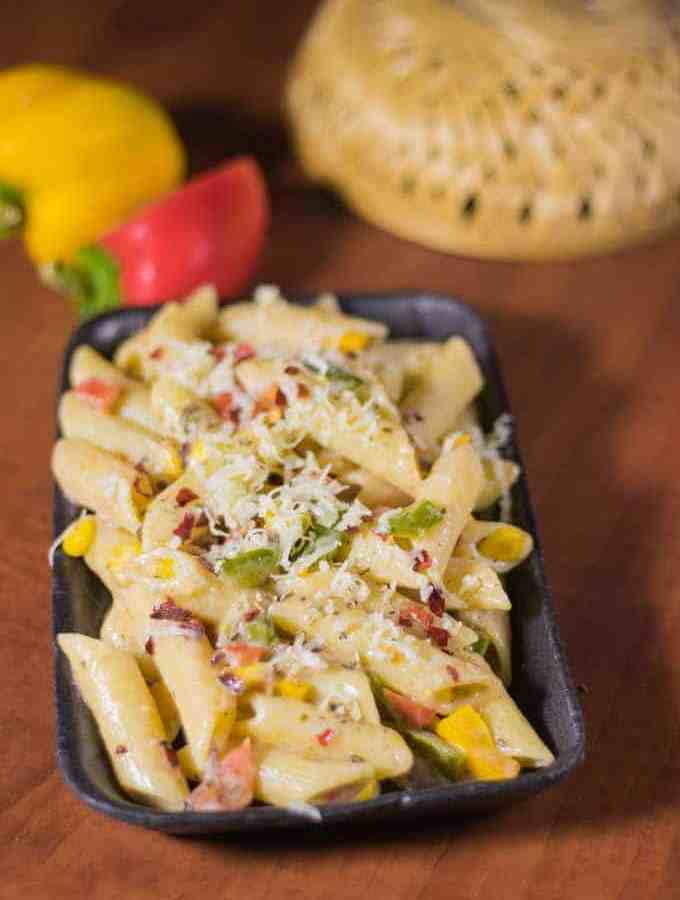 Italian white Sauce Pasta with some chilli flakes, grated cheese and Italian seasoning