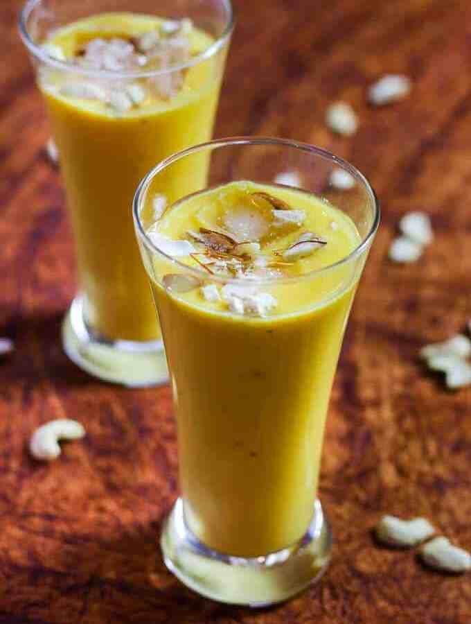 Mango Banana Smoothie on a glass with mango smoothie with some ice cubes, garnished with some cashew, almonds and saffron  