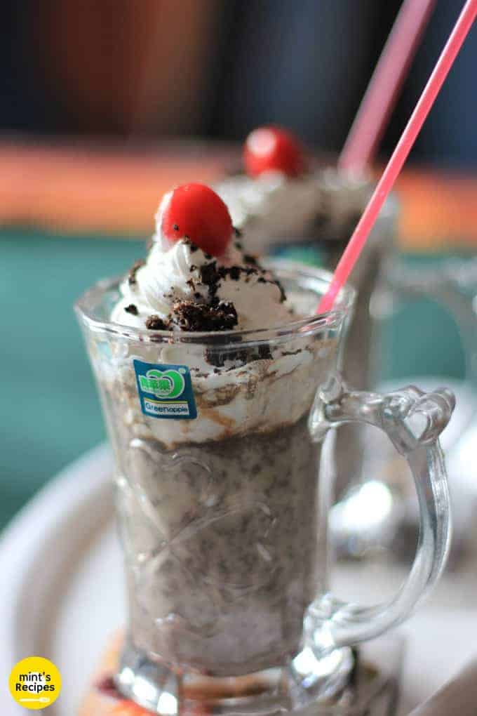 Oreo-Milk-Shake on a white surface with 2 glasses of milkshake decorated with some heavy cream with some oreo biscuit crush and a cherry on the top with a strow in it  