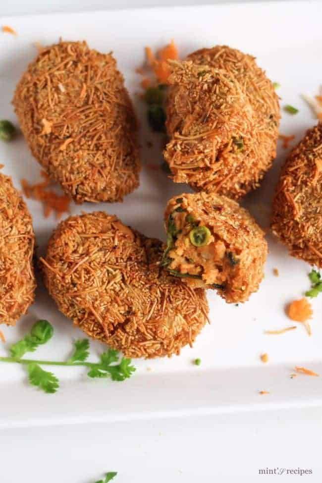 Potato Vermicelli Cutlet on a white rectangular plate with some grated carrots and some coriander leaves
