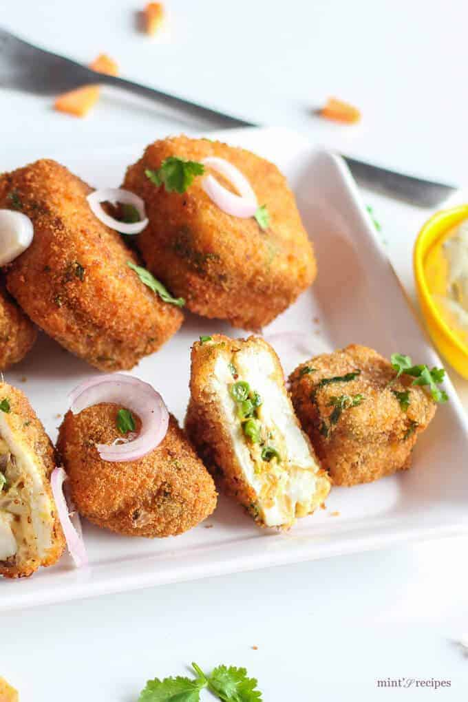Veg Paneer Cheese Bites With Mayo Dip on a white plate with some onion rings
