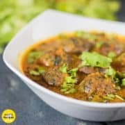 Palak paneer kofta curry on a white bowl with some sprinkles of coriander leaves and some coriander leaves and tomatoes kept on a black wooden surface |