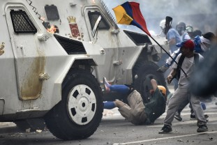 A charging National Guard riot control vehicle knocks down a demonstrator during a protest against Venezuelan President Nicolas Maduro, in Caracas on May 3, 2017. Venezuela's angry opposition rallied Wednesday vowing huge street protests against President Nicolas Maduro's plan to rewrite the constitution and accusing him of dodging elections to cling to power despite deadly unrest. / AFP PHOTO / Carlos BECERRA