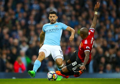 Ashley Young lunges at Sergio Aguero in the box
