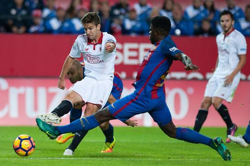 Sevilla's Argentinian forward Luciano Vietto (L) vies with Barcelona's French defender Samuel Umtiti during the Spanish league football match Sevilla FC vs FC Barcelona at the Ramon Sanchez Pizjuan stadium in Sevilla
