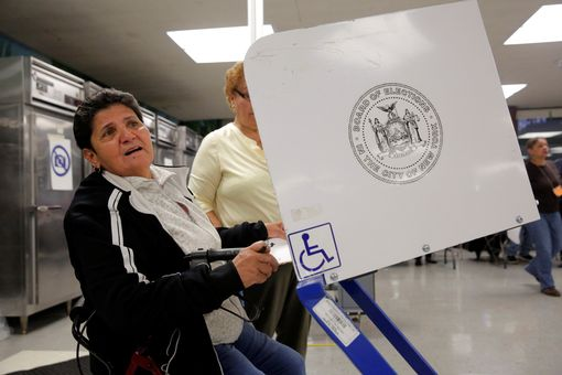 A woman fills out a ballot