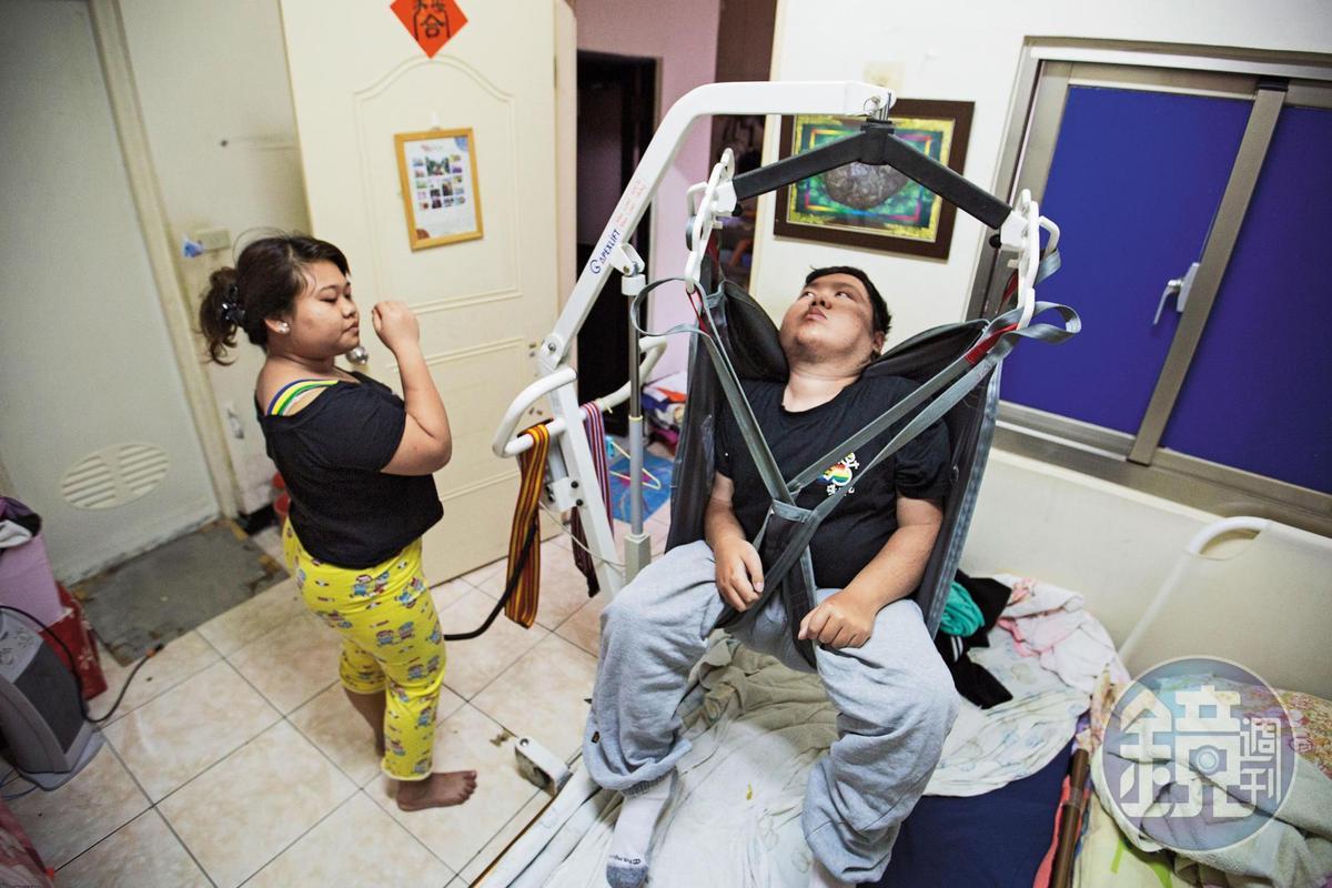 劉于濟(右)罹患肌萎症,無法自理生活,外傭24小時不離,晚上也須同房以便照顧。早上起床,外傭(左)需操作移位機,才能將他挪到輪椅上。