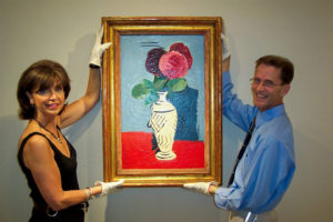"Sara Bogosian, left, and Michael Lally hang ""The Three Roses,"" by Arshile Gorky."