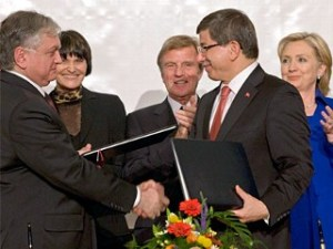 Armenia's Foreign Minister, Eduard Nalbandian, left, and Turkey's Foreign Minister, Ahmet Davutoglu, shake hands after signing the Protocols in the presence of Swiss Foreign Minister Micheline Calmy-Rey, French Foreign Minister, Bernard Kouchner and US Secretary of State, Hillary Rodham Clinton.