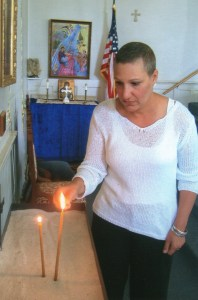 Susan Kulungian lights a candle at St. Gregory Church of North Andover for all those afflicted with breast cancer.