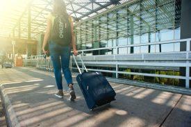 Eine Frau, die auf dem Weg in den Flughafen ist, einen Rucksack trägt und einen Koffer hinter sich herzieht