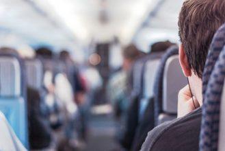 Ein Gang eines Flugzeugs, der verschwommen dargestellt ist, da ein Mann von hinten auf seinem Sitz im Fokus steht