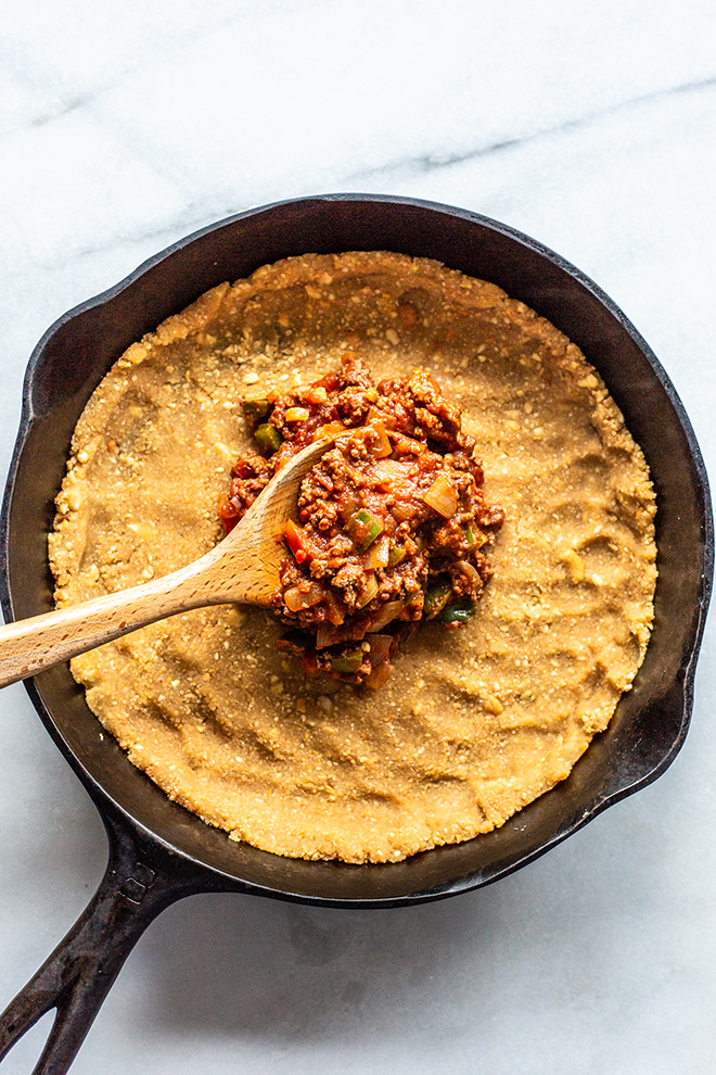 whole30 pie crust with a scoop of taco filling in a skillet on a white marble background