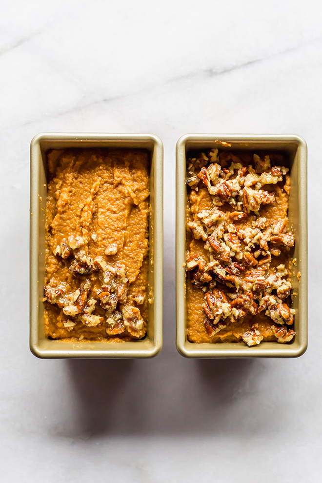 unbaked mini pumpkin bread loaves with crumble on a white marble board.