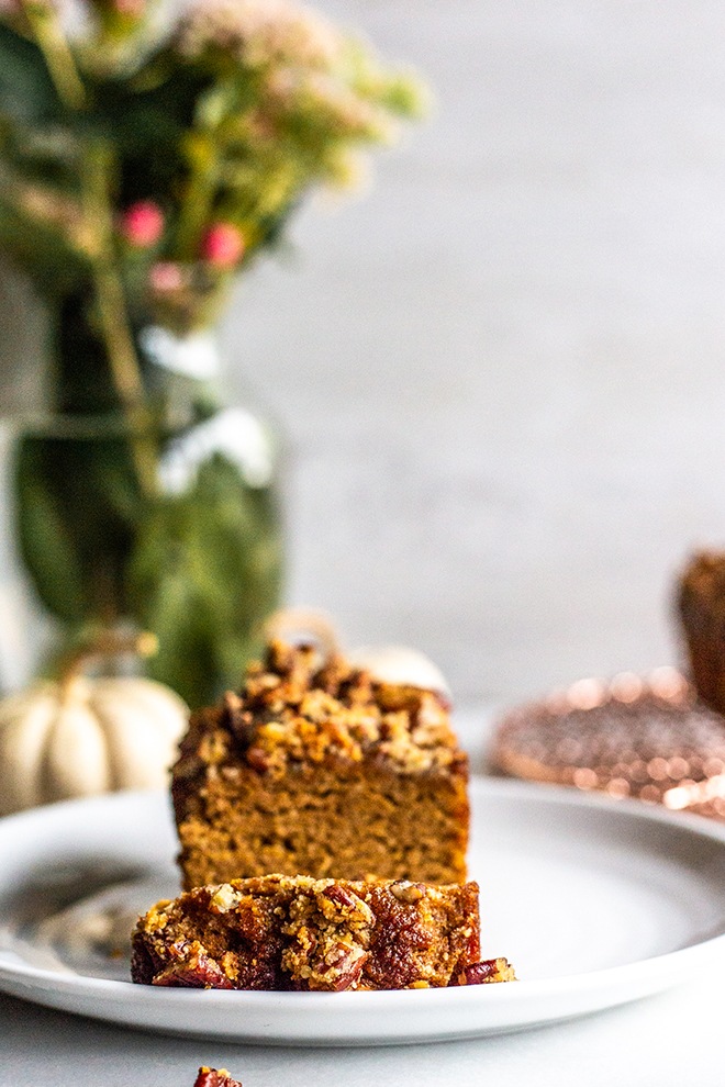 mini pumpkin bread with a flower arrangement and bread on a white plate