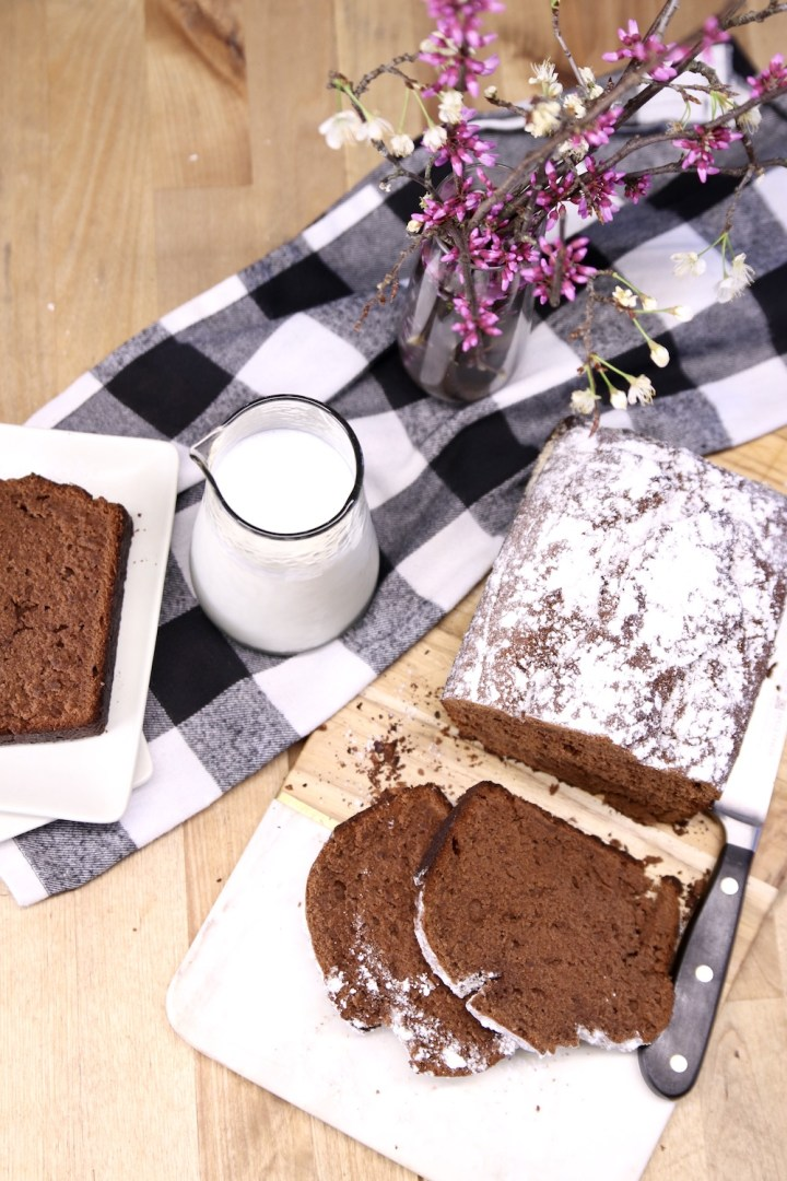 Sliced banana bread with loaf, jar of  milk, vase of red bud stems, black and white napkin