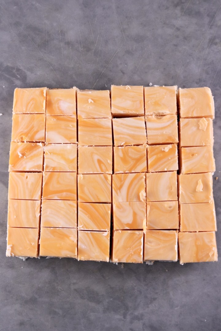 Creamsicle Fudge cut into squares on a gray cutting board