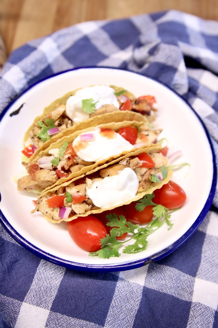 plate of 3 chicken tacos on a blue check towel