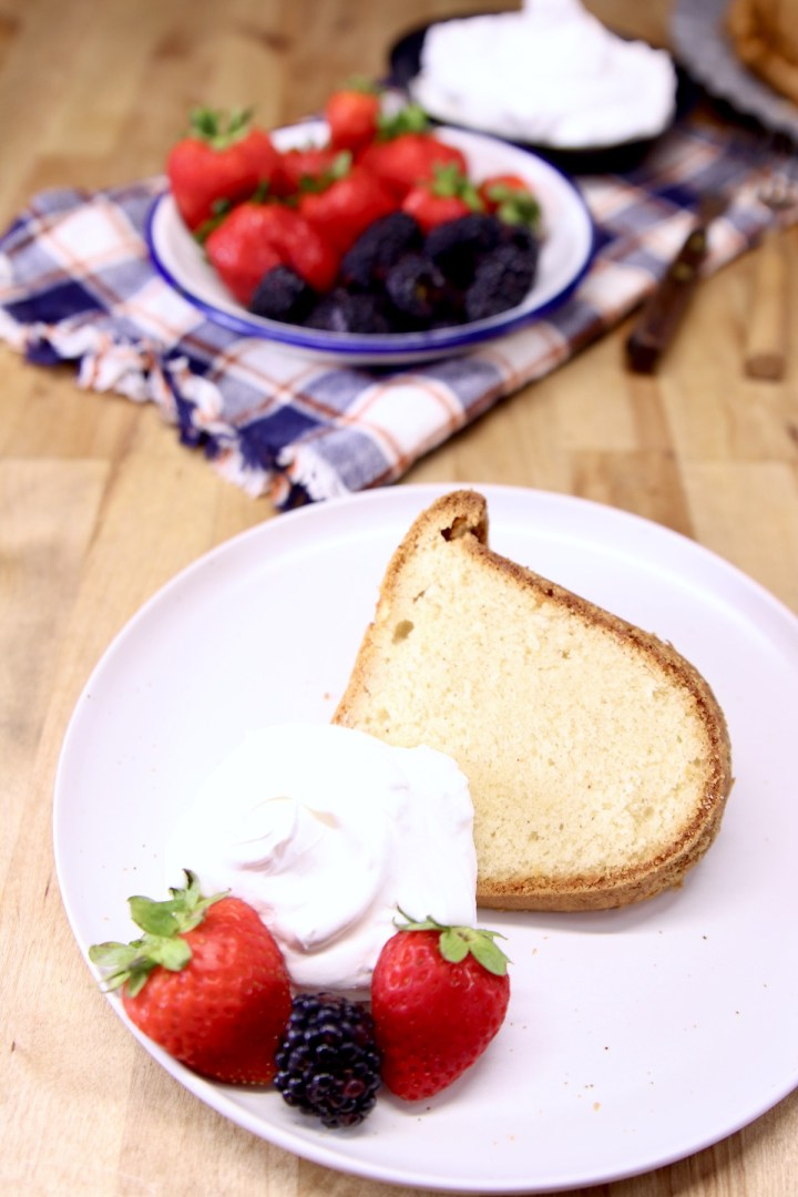 plate with sliced pound cake, whipped cream, berries