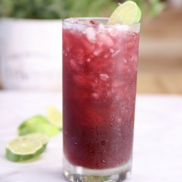 Pomegranate Margarita in a tall glass with lime wheel