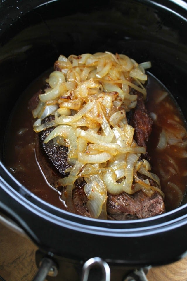 Beef pot roast in slow cooker topped with caramelized onions