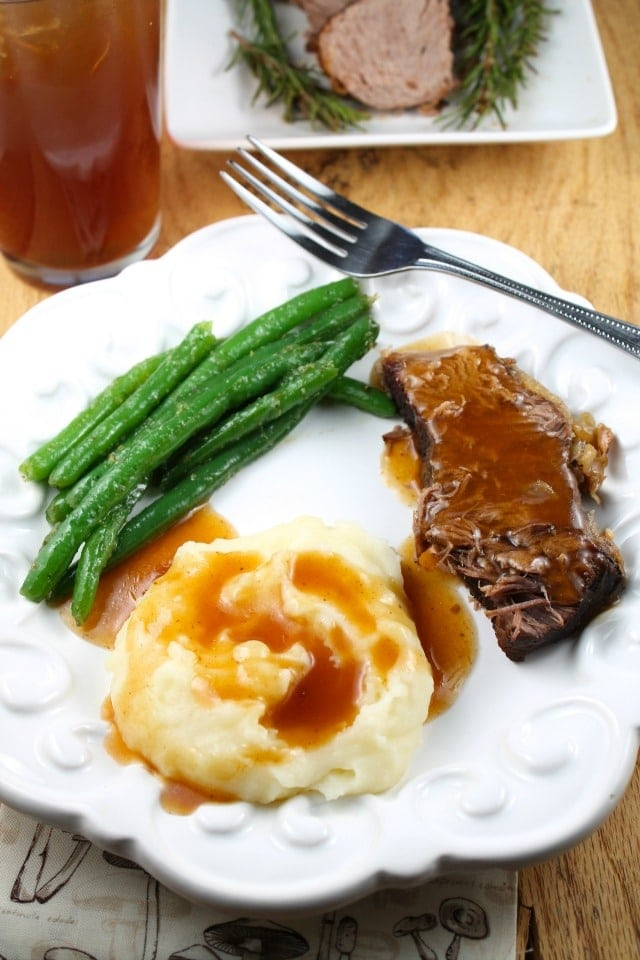 Pot Roast slice with gravy, mashed potatoes topped with gravy and green beans on a plate with a glass of tea