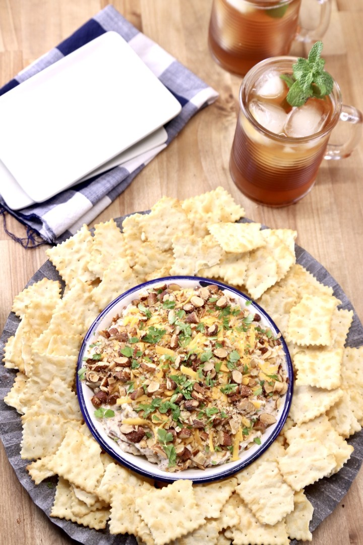 party dip on a platter with chips, 2 glasses iced tea, small appetizer plates