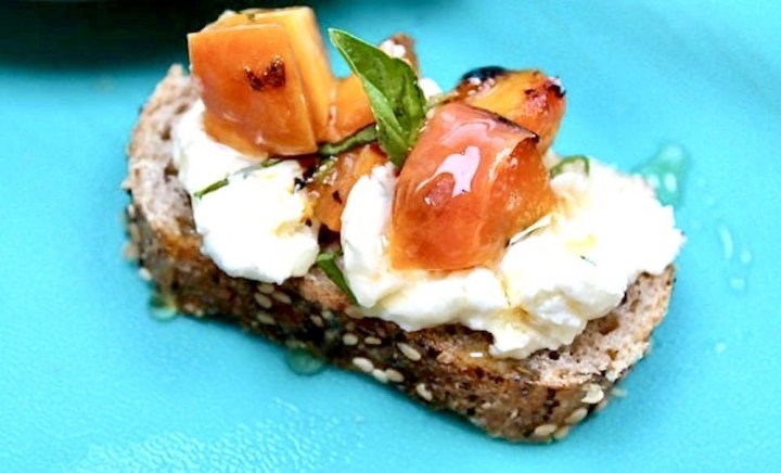 slice of toasted bread with cream cheese, peaches, basil and honey