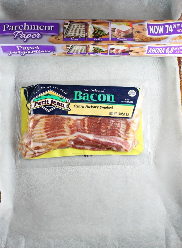 Package of Petit Jean Bacon on a parchment lined baking sheet with parchment paper box