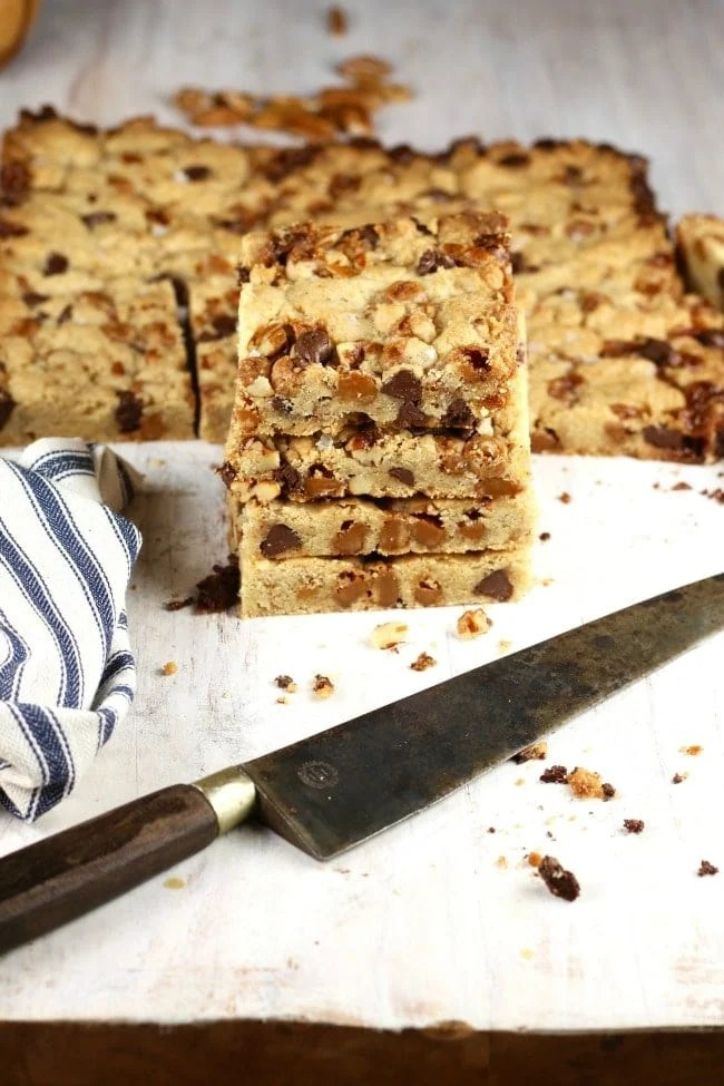 stack of salted caramel cookie bars with knife and napkin