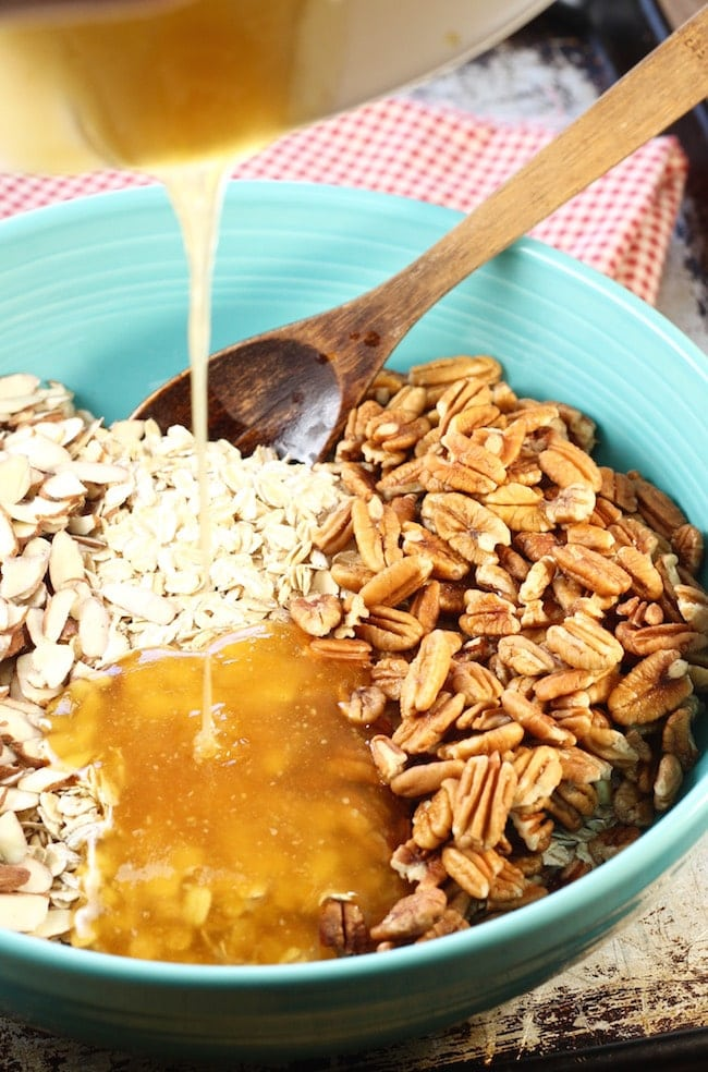 Pouring honey and oil mixture over bowl of oats, pecans and almonds