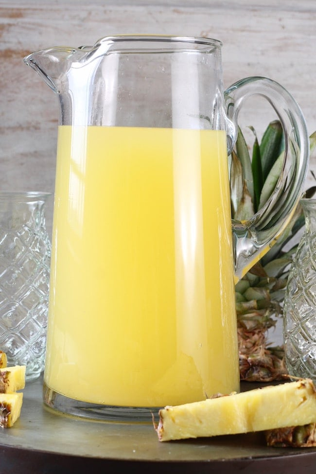 Glass Pitcher of Easy Pineapple Wine Punch with fresh pineapple wedges