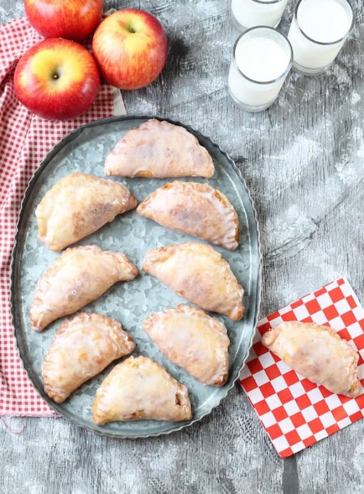 Galvanized platter of fried apple hand pies with fresh apples, glasses of milk and a pie on a red check paper