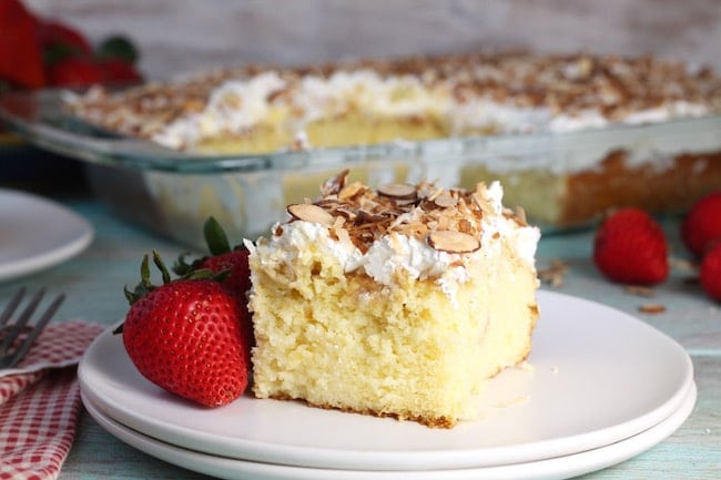 Slice of easy Coconut Cream Cake on a plate with whole strawberries with cake pan in the background