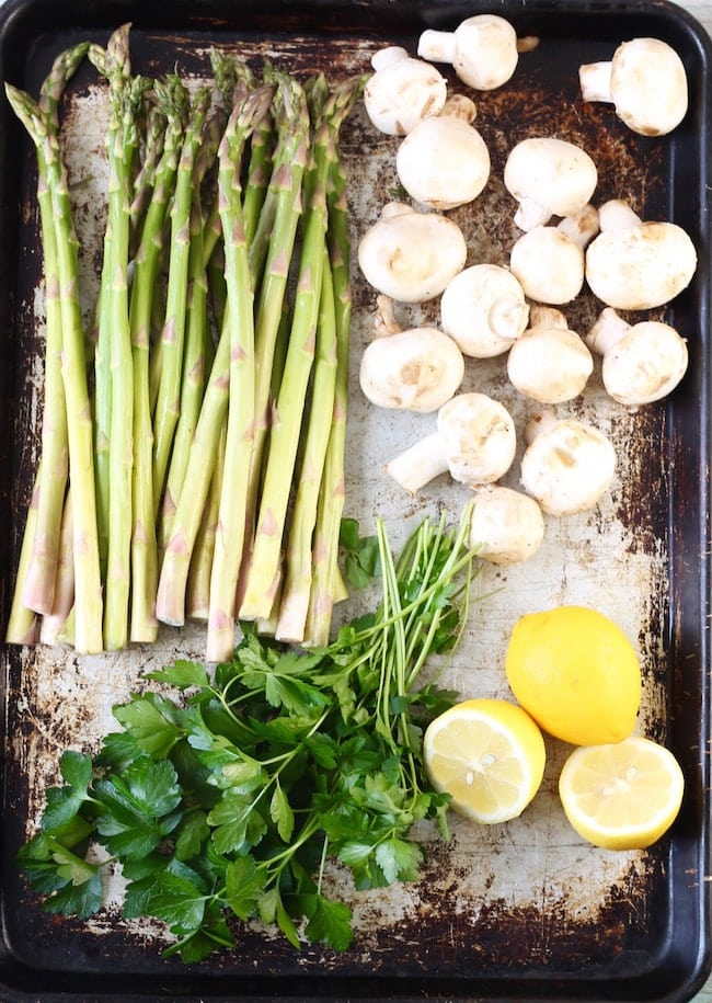 Fresh asparagus, mushrooms, parsley and lemons on a sheet pan
