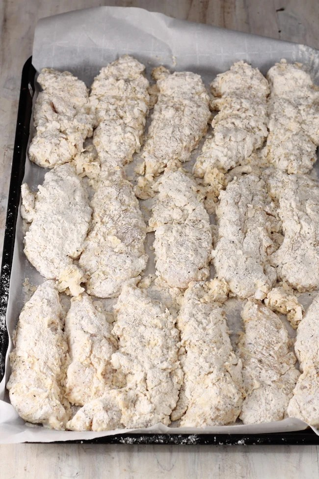 Battered Chicken Tenders on parchment paper ready for the fryer